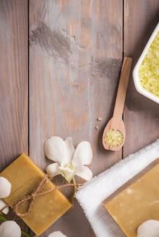 Спа-набор. натуральное органическое мыло ручной работы и белая орхидея на деревянном фоне