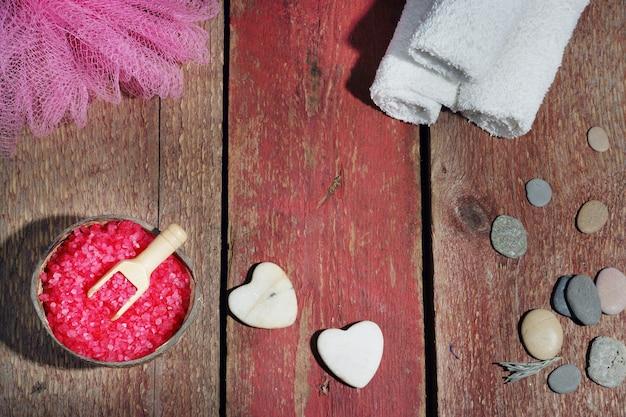 木製の赤い背景、バスソルト、ヘチマ、白いタオルとハートの形の石の上に設定されたスパ