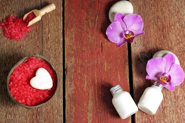 赤いバスソルト、肌用ローション、石に蘭の花が飾られた木製のテーブルに置かれたスパ、テキスト用のコピースペース。