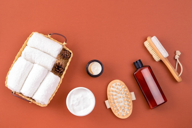 Spa set towels massaging brush body cream on brown surface eco zero waste concept relax spa massage