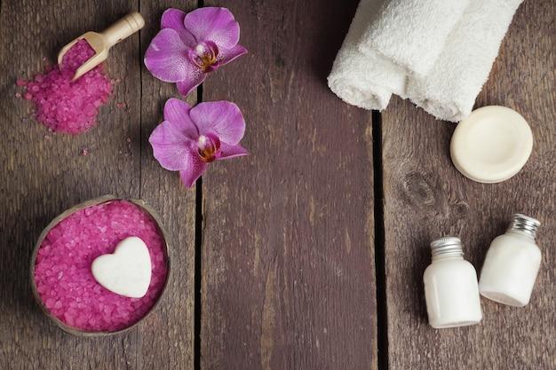 バスソルト、蘭とタオルの花、ローションと石鹸が木製の背景に設定されたスパ