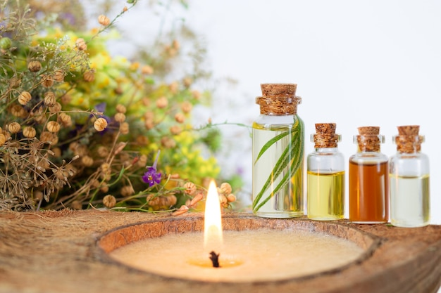 Spa set with burning candle, essential oils in bottles, herbs and flower