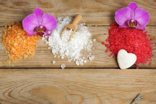 Спа-набор с разноцветными горками из морской соли для ванн и цветов орхидей на деревянном фоне