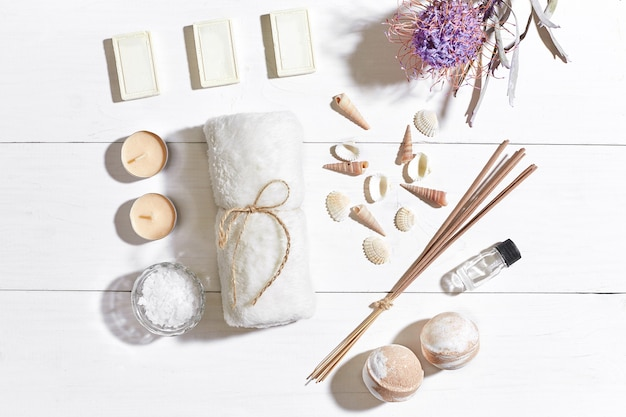Spa set with sea salt essential oil soap and towel decorated with dry flower on white wooden background