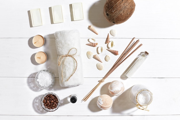 Spa set with sea salt, essential oil, soap and towel decorated with seashells on white wooden background. top view. copy space. still life. mock-up. flat lay
