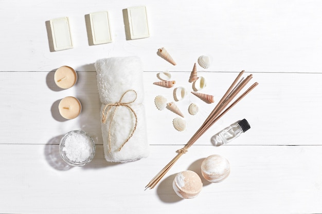 Spa set with sea salt essential oil soap and towel decorated with seashells on white wooden background