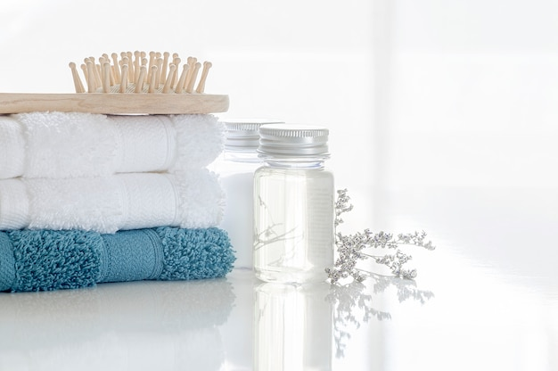 Spa set with stack of clean towels, oil bottle, wooden comb and flower