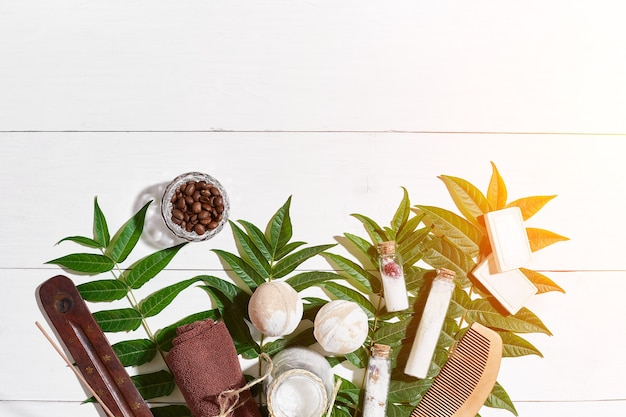 Spa set with towel and soap on white wooden background with green leaves sun flare