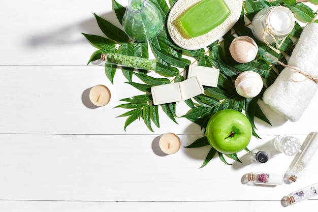 Spa set with towel and soap on white wooden background with green leaves