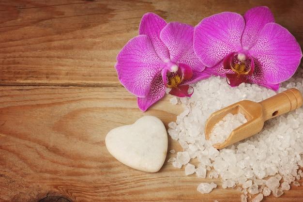 白い海の塩、木のへら、明るい蘭の花、ハート型の石がセットされたスパ