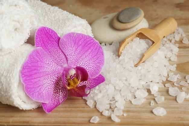 白いタオル、海の塩、木のへら、明るい蘭の花がセットされたスパ