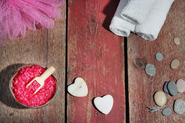 Spa set on a wooden red background, bath salt, loofah, white towels and stones in the form of hearts