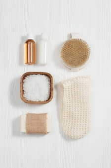 Spa setting for body care and beauty treatment on white wood bottles, soap, sea salt, washcloth for bath.