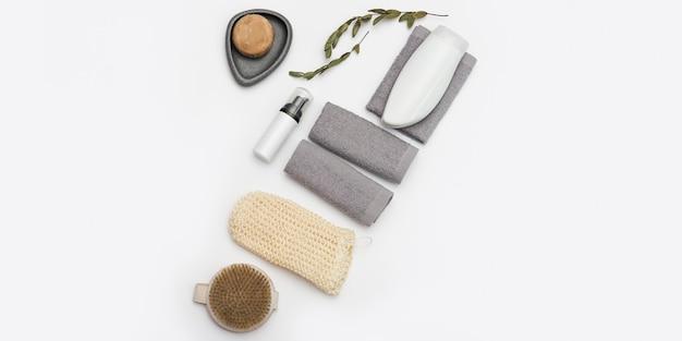 흰색 바탕에 바디 케어 및 미용 치료를위한 스파 설정입니다. 비누,면 타월, 목욕용 수건, 나무 빗. 복사 공간, 평평하다