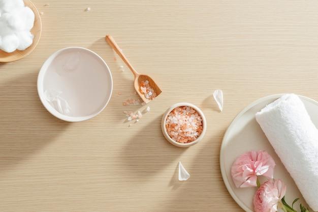 Настройка спа соли, полотенца, цветка на тарелке на деревянной предпосылке с космосом экземпляра. расслабиться. закройте вверх. вид сверху.