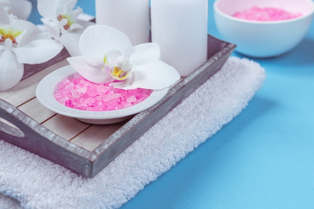 Spa setting still life with orchid flower , candle, soap and towels on blue background