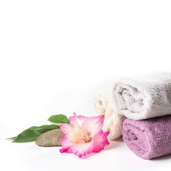 Spa setting of towel, flower isolated on white with copy space.