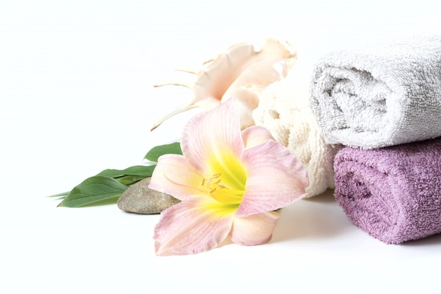 Spa setting of towel, flower on white with copy space. close up.