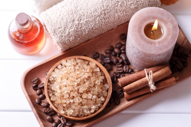 Spa setting with aromatic candle, coffee bath salt, soft cotton towels and essential massage oil