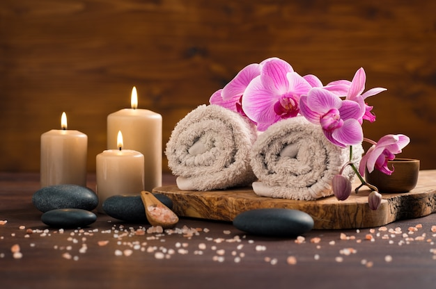 Spa setting with brown rolled towel and orchids and candles on wood.