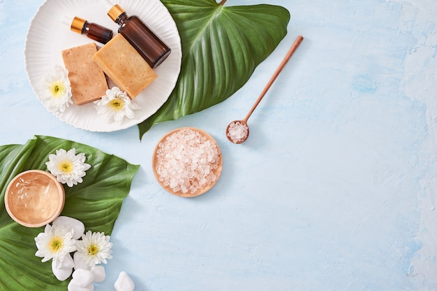 Spa setting with cosmetic cream, gel, bath salt and fern leaves on blue background