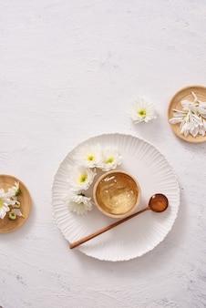 Установка спа с косметическим гелем, листья на белом фоне стола