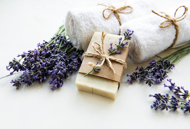 Spa setting with natural soap, towels and lavender on a marble background