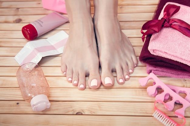 Спа. уход за кожей женских ножек красавицы с красными розами, полотенцем и кремом