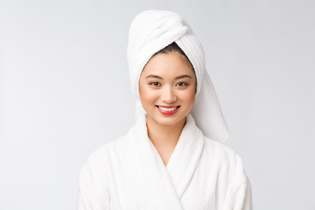 Spa skincare beauty asian woman drying hair with towel on head after shower treatment. beautiful multiracial young girl touching soft skin.