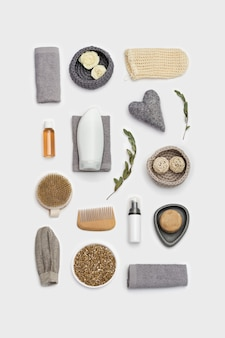 Spa still life background. set for body care on white surface. bottles with gel or shampoo, soap, wooden comb, washcloth for bath, sea salt.