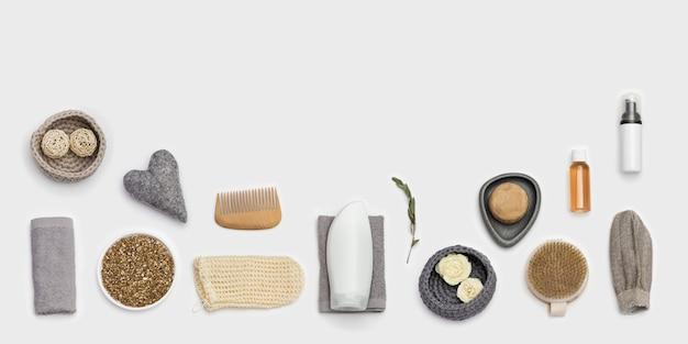 Спа натюрморт фон. набор для ухода за телом на белой поверхности. бутылки с гелем или шампунем, мыло, деревянная расческа, мочалка для ванны, морская соль.