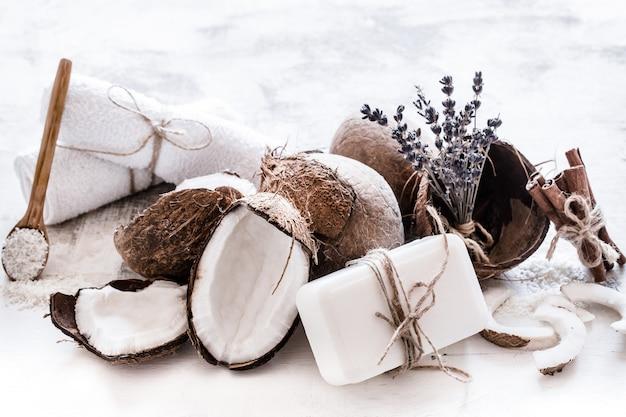 Спа-натюрморт из органической косметики с кокосами на светлом деревянном фоне, концепция ухода за телом