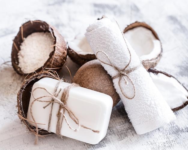 Spa ancora in vita di cosmetici biologici con noci di cocco su uno sfondo di legno chiaro, concetto di cura del corpo