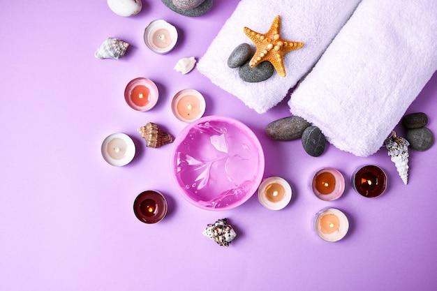 촛불, 돌, 바다 조개 불가사리와 분홍색 배경에 수건으로 스파 정물 치료, 텍스트 복사 공간, 스킨 케어 제품, 가정용 스파 치료를위한 천연 화장품