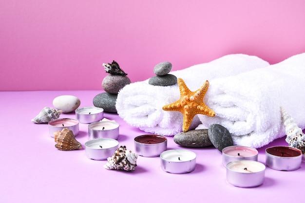 촛불, 돌, 바다 포탄 불가사리와 분홍색 배경에 수건 스파 정 치료, 텍스트 복사 공간