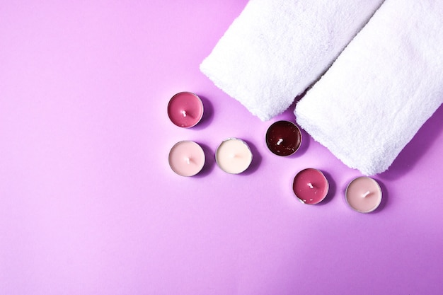 Spa still life treatment with candles and towels on pink background, copy space for text