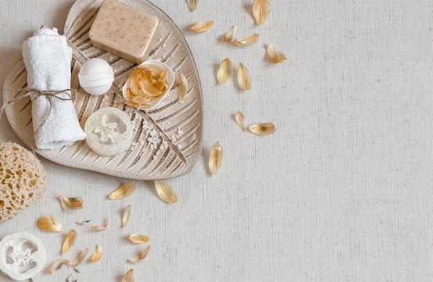 Spa ancora in vita con accessori da bagno per la cura del corpo tra i petali di fiori vista dall'alto. concetto di salute e igiene.