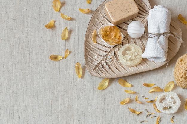 Спа-натюрморт с банными принадлежностями для ухода за телом среди вид сверху лепестков цветов. концепция здоровья и гигиены.