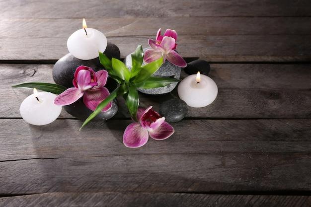 나무 테이블에 아름 다운 꽃과 촛불으로 스파 정