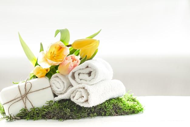 Натюрморт спа с натуральным мылом, полотенцами и желтыми тюльпанами на светлом размытом фоне копией пространства.