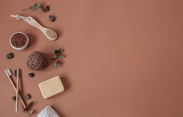 Spa still life with natural toothbrushes, scrub, soap and decorative details flat lay
