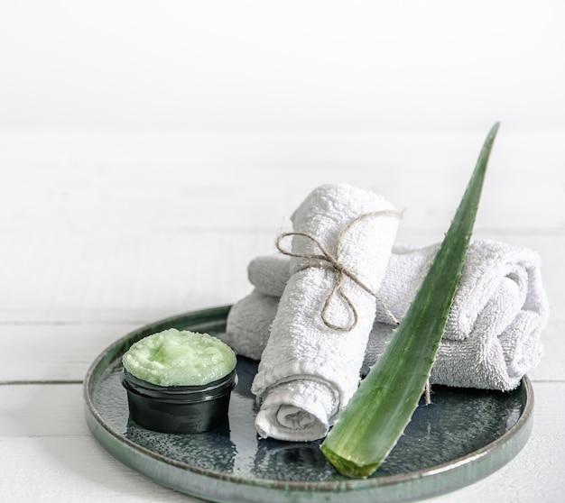 オーガニックスキンケア、新鮮なアロエの葉、タオルを備えたスパの静物画。美容とオーガニック化粧品のコンセプト。