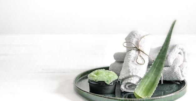 Натюрморт спа с органическими средствами по уходу за кожей, свежими листьями алоэ и полотенцами.