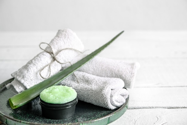 Spa still life with organic skincare, fresh aloe leaf and towels. the concept of beauty and organic cosmetics  background