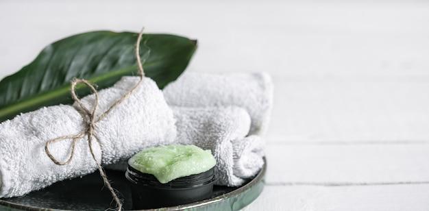 オーガニックスキンケア、天然の葉とタオルのコピースペースを備えたスパの静物。美容とオーガニック化粧品のコンセプト。