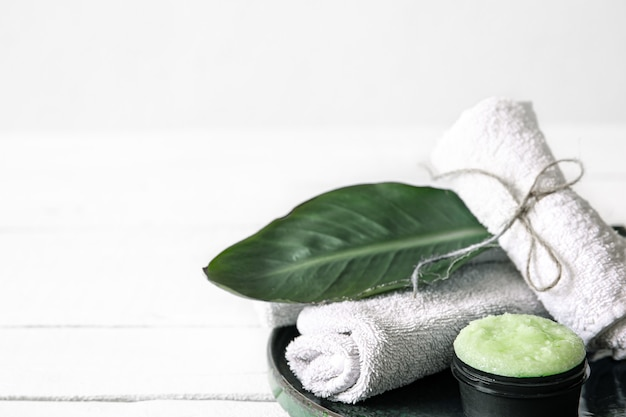 オーガニックスキンケア、天然の葉、タオルを備えたスパの静物画。美容とオーガニック化粧品のコンセプト。