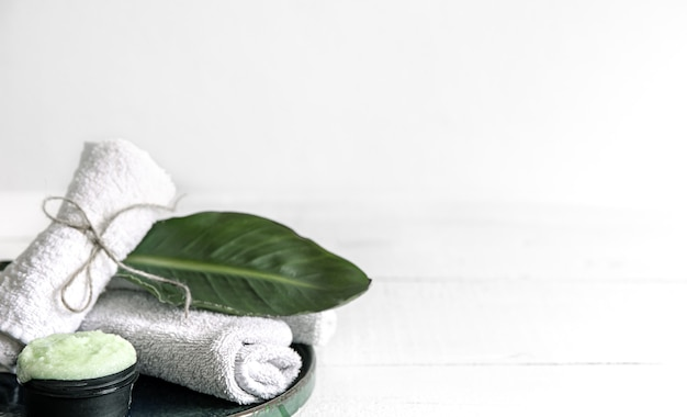 Натюрморт спа с органическими средствами по уходу за кожей, натуральными листьями и полотенцами.