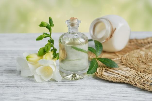 가벼운 표면에 프리지아 꽃으로 둘러싸인 향수와 아로마 오일 병이있는 스파 정물