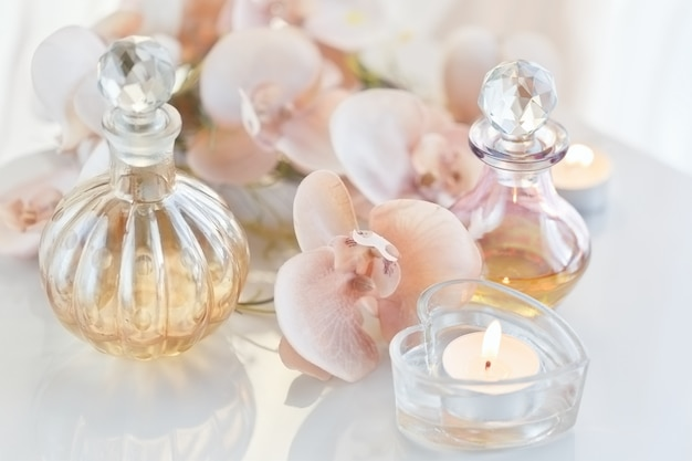 Spa still life with perfume and aromatic oils bottles surrounded by flowers and candles