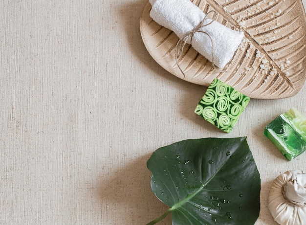 Spa still life with soap, towel, leaf and sprinkled sea salt top view. hygiene and beauty concept.